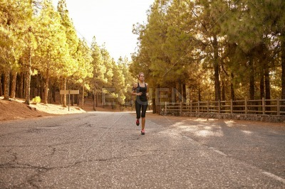 Young brunette woman running in forest
