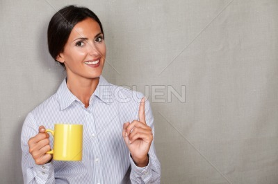 Young businesswoman smiling and holding hot drink