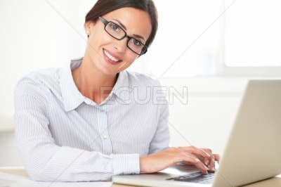 Young cheerful secretary using her laptop