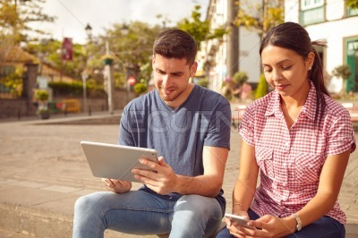 Young couple looking at their tablet and cellphone