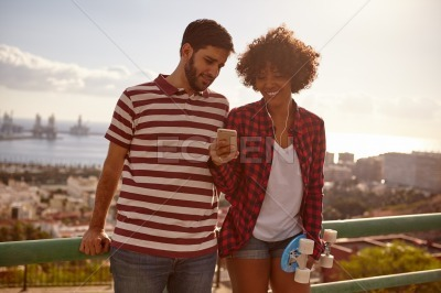 Young couple on bridge with cell phone