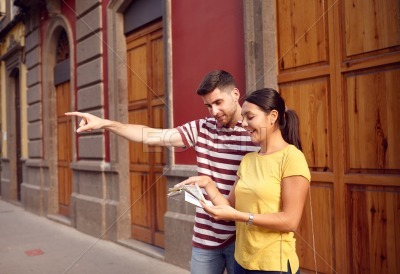 Young couple pointing and studying map