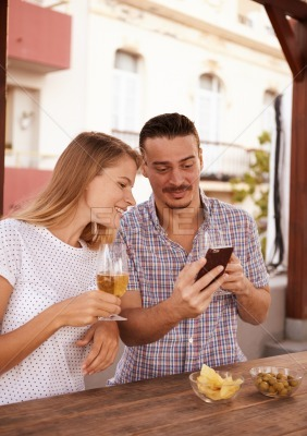 Young couple with beers and cellphone