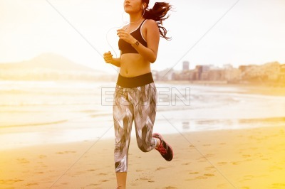 Young female body running along beach