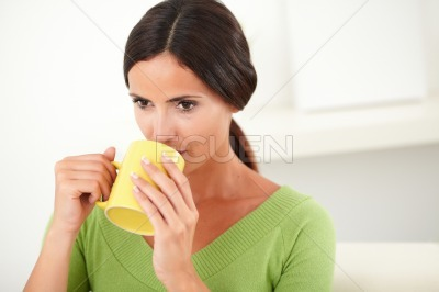 Young female drinking from a yellow mug