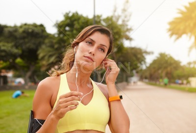 Young female runner listening to music outdoors