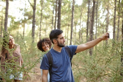 Young friends taking pictures in forest
