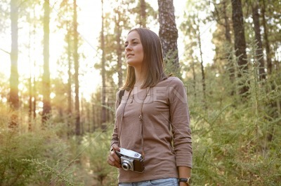 Young girl with camera in the woods