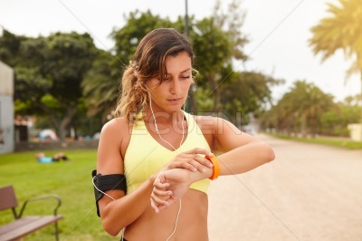 Young jogger looking at smart bracelet outdoors
