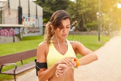 Young jogger looking at smart watch while standing