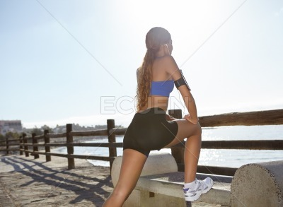 Young jogger stretching on the coastline