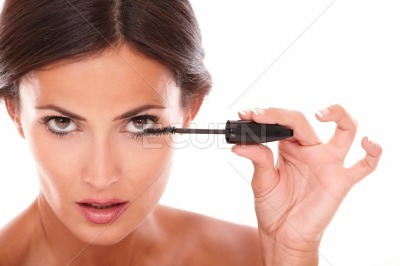 Young latin woman using mascara to her eyelash