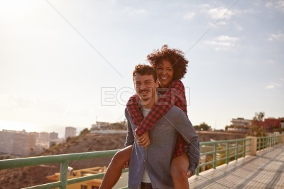 Young man giving his girl a piggyback