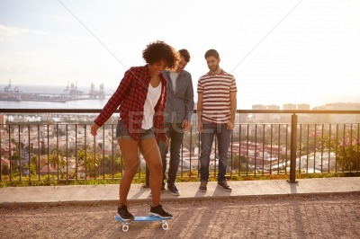 Young men watching a girl skateboarding