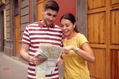 Young tourist couple finding their location on map