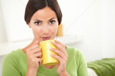 Young woman blowing on hot coffee