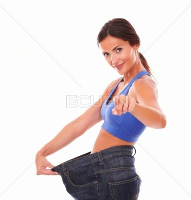 Young woman looking at you and pulling jeans