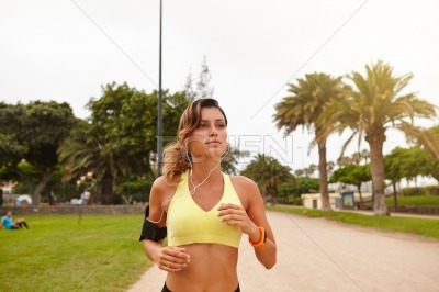 Young woman running while listening to music