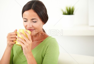 Young woman smelling a cup of coffee