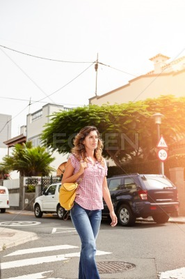 Young woman walking down a brightly lit street