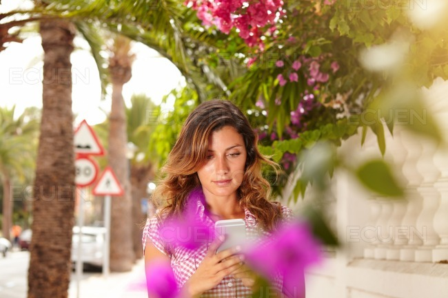 Beautiful lady browsing the internet on cell phone