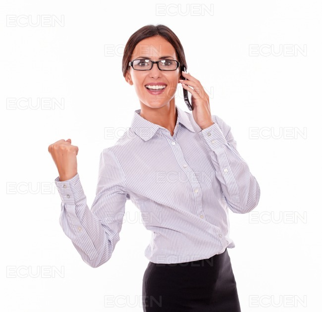 Celebrating brunette businesswoman with cell phone stock photo