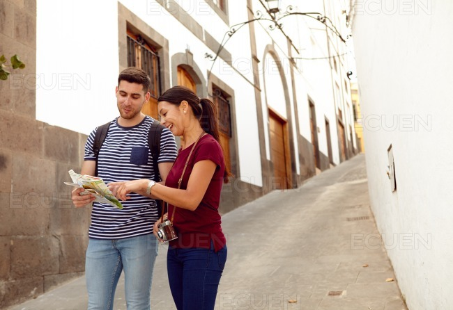 Couple on vacation with a backpack studying a map stock photo
