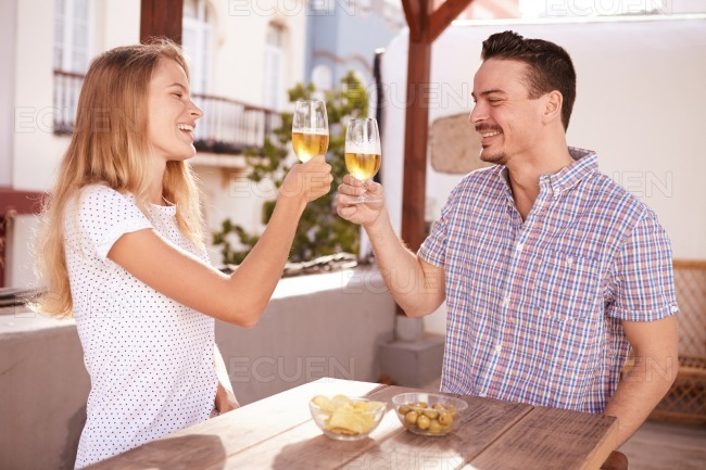 Couple raising and clinking their glasses stock photo