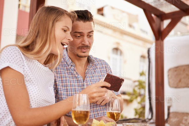 Cute couple looking at cellphone surprised stock photo