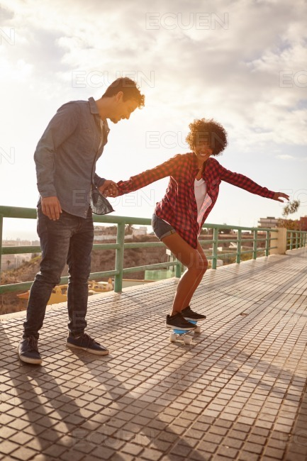 Girl learning to skateboard from boy stock photo