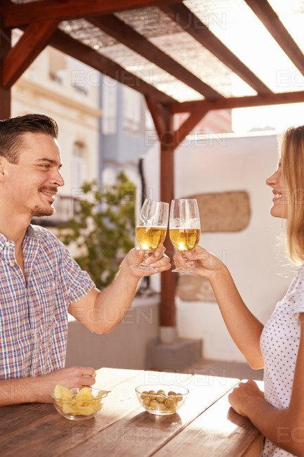Good looking couple raising their glasses together