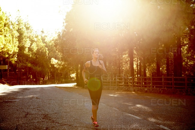 Healthy young brunette woman jogging alone stock photo