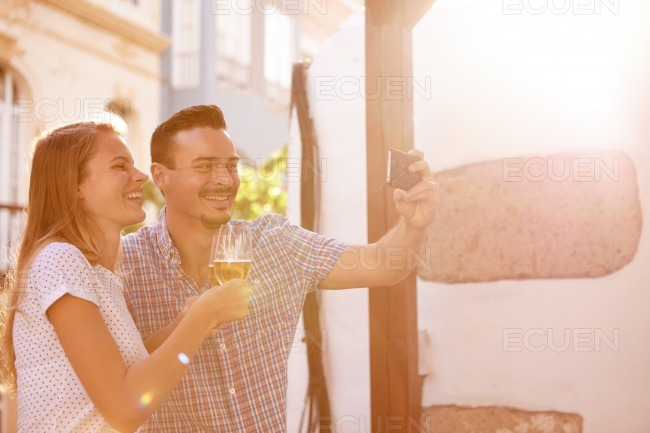 Laughing couple with beers taking selfie
