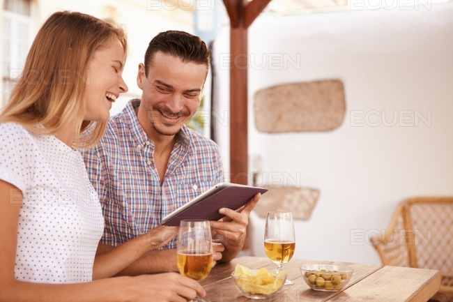 Laughing couple with touchpad and beers stock photo