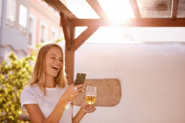 Pretty blond girl with beer and cellphone stock photo