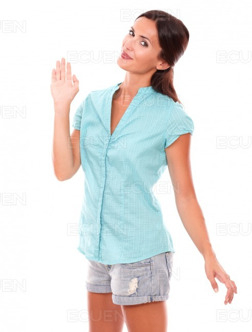 Pretty brunette lady in shorts gesturing greeting stock photo