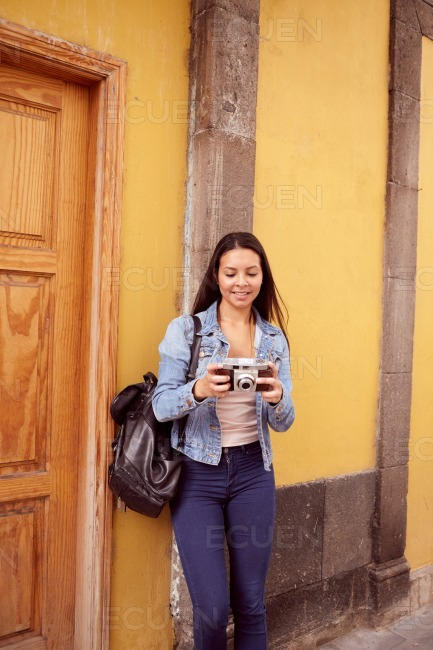 Pretty young girl leaning against a grey pillar stock photo
