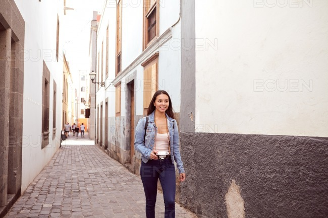 Pretty young lady walking hurriedly with backpack stock photo