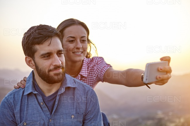 Smiling young couple taking a selfie stock photo
