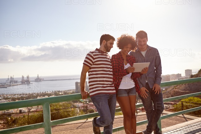 Three friends leaning against a railing stock photo