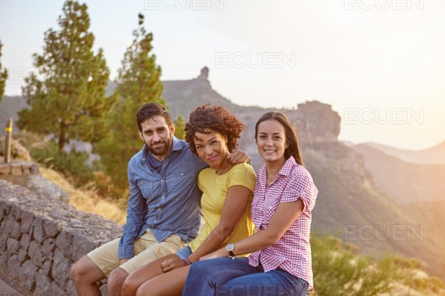 Three friends sitting on a stone wall stock photo