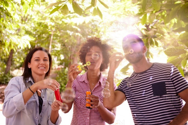 Three funlovers blowing bubbles and laughing stock photo