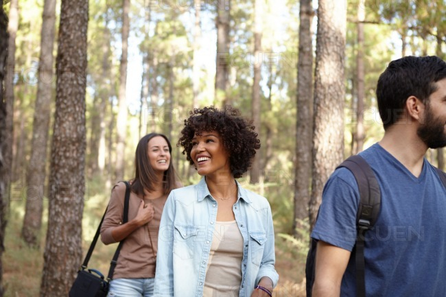 Three laughing friends in a forest stock photo