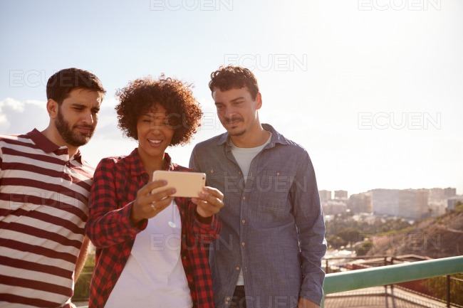 Three young millennials looking at cellphone stock photo