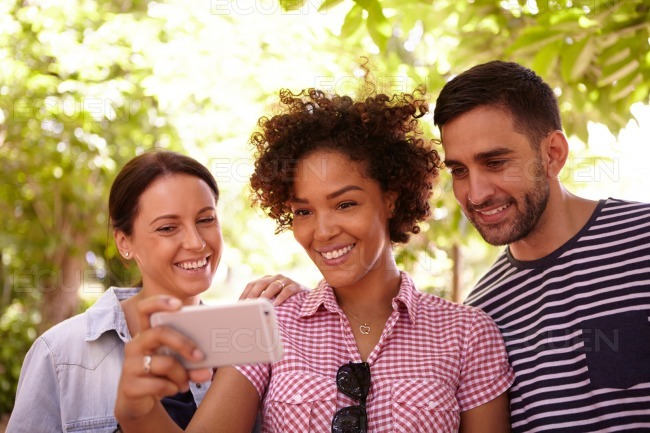 Three young people looking at a cellphone stock photo