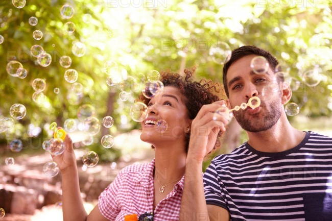 Two happy young friends blowing bubbles stock photo