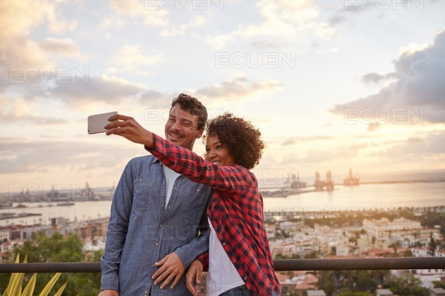 Young couple on bridge taking selfie stock photo