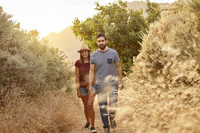 Young couple walking on a mountain path stock photo