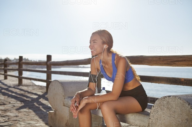 Young female jogger resting on the coastline stock photo