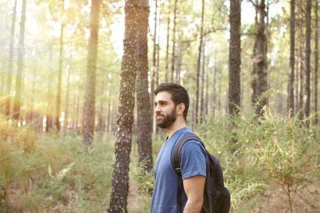 Young guy standing in the forest stock photo